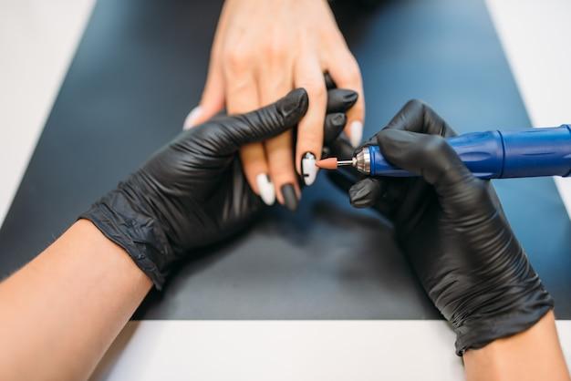 Esteticista com luvas segura uma máquina de polir e limpa verniz velho das unhas de uma cliente, vista de cima