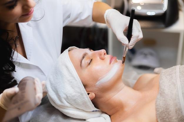 Esteticista com um pincel aplica uma máscara hidratante branca no rosto de uma jovem cliente em um salão de beleza de spa