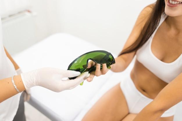 Esteticista dá óculos de proteção para paciente do sexo feminino antes do procedimento de remoção de cabelo a laser