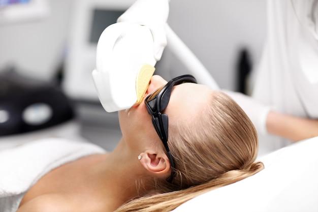 Esteticista dando tratamento a laser de depilação para mulher no rosto