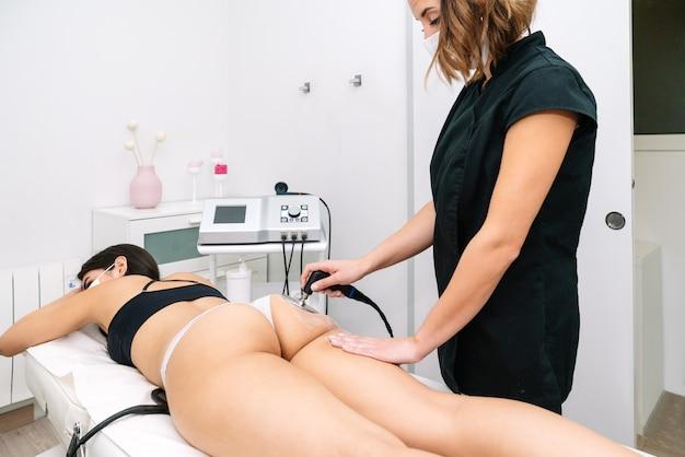 Esteticista dando tratamento de radiofrequência a uma mulher nas nádegas que estimula o funcionamento de células saudáveis