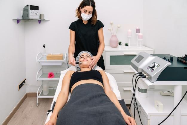Esteticista dando tratamento de radiofrequência no rosto de uma mulher que rejuvenesce e estimula o funcionamento celular saudável