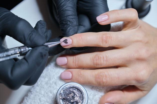 Esteticista de close-up, pintura arte design nas unhas.