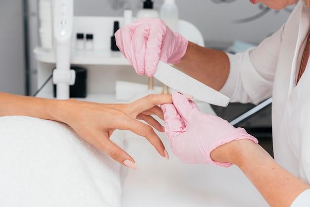 Esteticista de higiene e cuidado das unhas usando luvas
