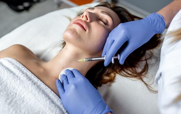 Esteticista de menina aplica injeções nos lábios e no rosto de uma linda mulher em uma cunha cosmética. conceito de cosmetologia.