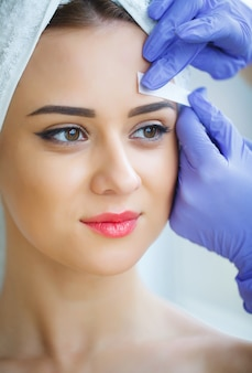 Esteticista depilação de sobrancelhas de mulher jovem no centro de spa