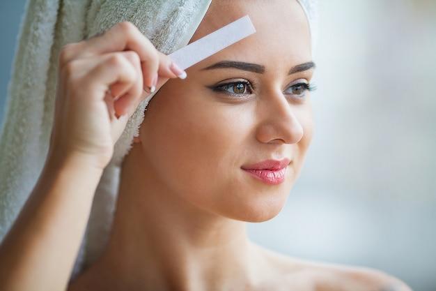 Esteticista depilação sobrancelhas de mulher jovem em centro de spa