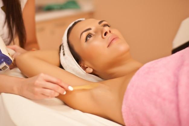 Esteticista depilando axilas femininas em centro de spa