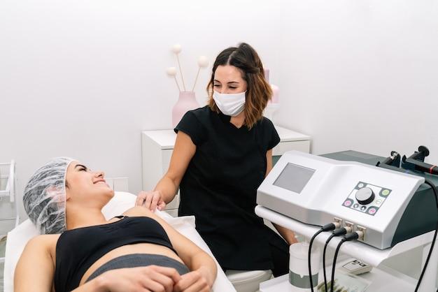 Esteticista e cliente falando depois de dar a ela um tratamento de rejuvenescimento com máscara facial e corporal para protegê-la da pandemia de coronavírus covid19 de 2020