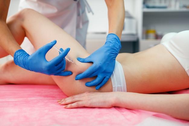 Esteticista em luvas dá injeção de botox na coxa em paciente do sexo feminino na mesa de tratamento. procedimento de rejuvenescimento em salão de esteticista.