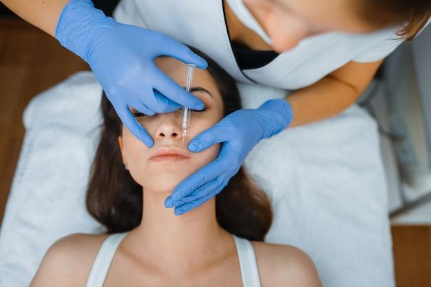 Esteticista em luvas dá injeções de botox facial em paciente do sexo feminino na mesa de tratamento procedimento de rejuvenescimento em salão de esteticista. médico e mulher, cirurgia estética contra rugas