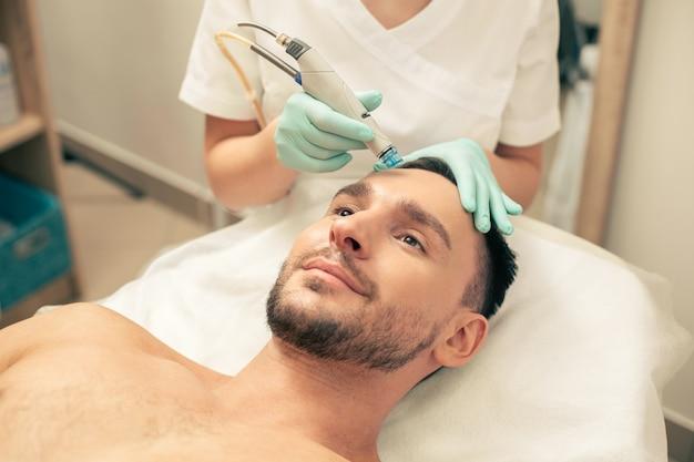Esteticista em luvas de borracha segurando um utensílio moderno enquanto nutre a pele de um homem sorridente com hidratantes intensos