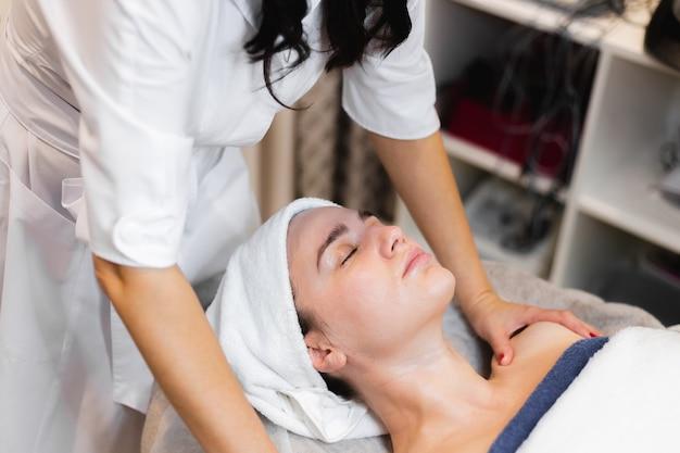 Esteticista em um salão de beleza de spa aplica creme no rosto de uma cliente, uma garota deitada em uma mesa de cosmetologia