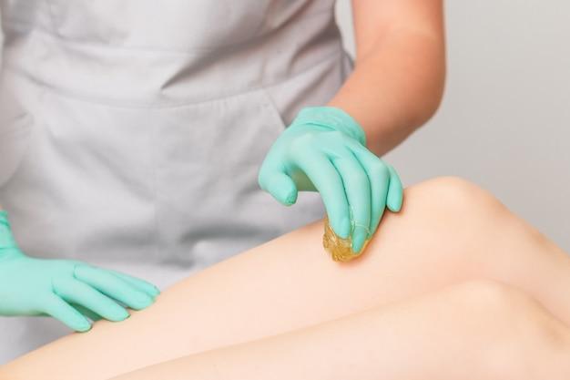 Esteticista encerando as pernas da mulher no centro de spa.