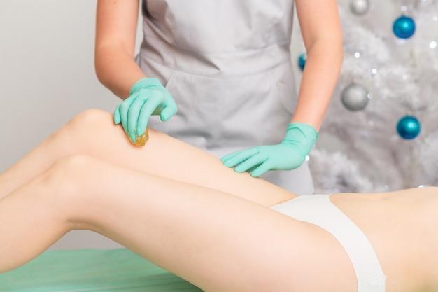 Esteticista encerando as pernas femininas no centro de spa.