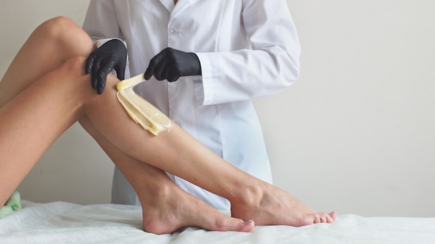 Esteticista faz depilação com pasta de açúcar no spa studio