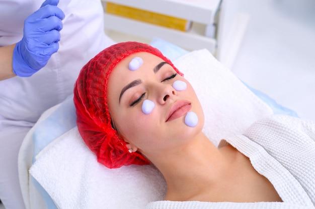 Esteticista faz limpeza e esfoliante facial para linda garota. salão de beleza.