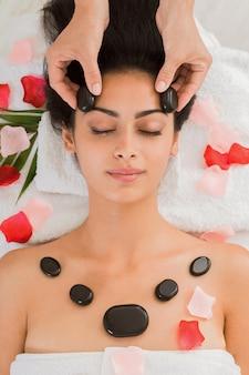 Esteticista faz massagem com pedras para mulher no centro de bem-estar, vista superior
