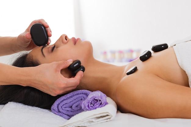 Esteticista faz massagem com pedras para mulher no centro de bem-estar