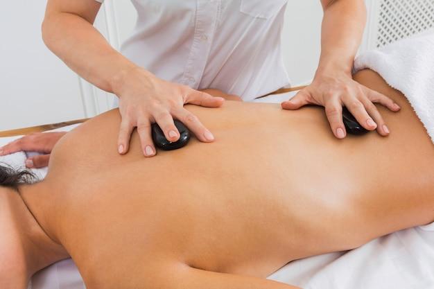 Esteticista faz massagem com pedras spa para mulher no centro de bem-estar