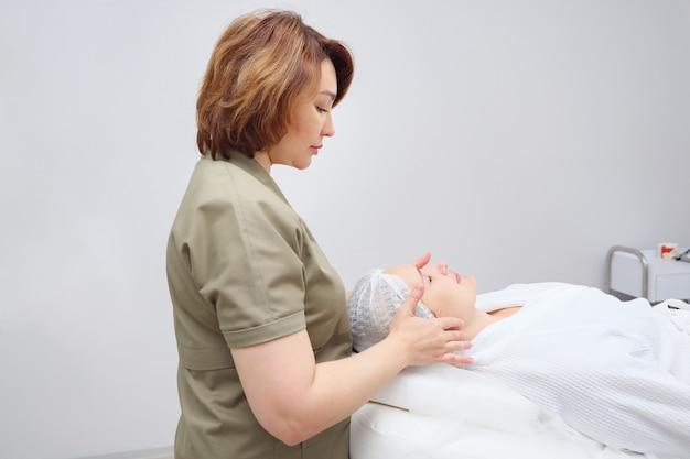 Esteticista faz massagem facial profissional vista lateral