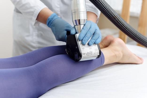 Esteticista faz massagem glp nas pernas de uma jovem de terno roxo. massagem de drenagem linfática. tratamentos de emagrecimento.