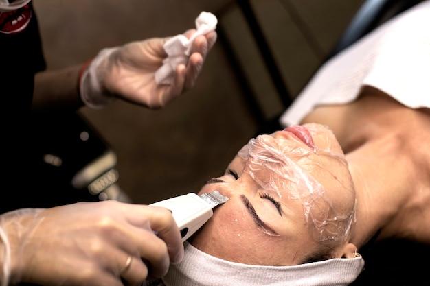 Esteticista faz procedimentos de limpeza de pele de menina