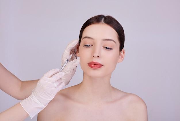 Esteticista faz procedimentos para injeções no rosto de uma jovem mulher.