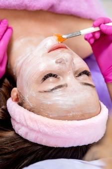 Esteticista faz uma máscara de argila facial contra acne no rosto de uma mulher para rejuvenescer a pele. tratamento de cosmetologia da pele problemática no rosto e no corpo.
