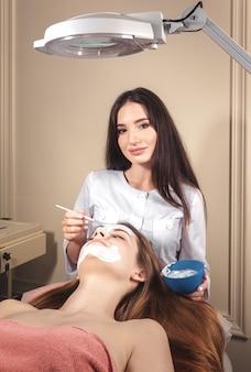 Esteticista faz uma máscara facial para o paciente