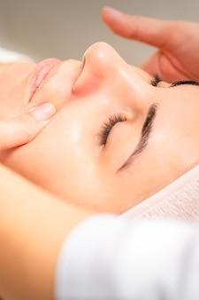 Esteticista fazendo massagem facial de drenagem linfática ou massagem de lifting no salão de beleza.