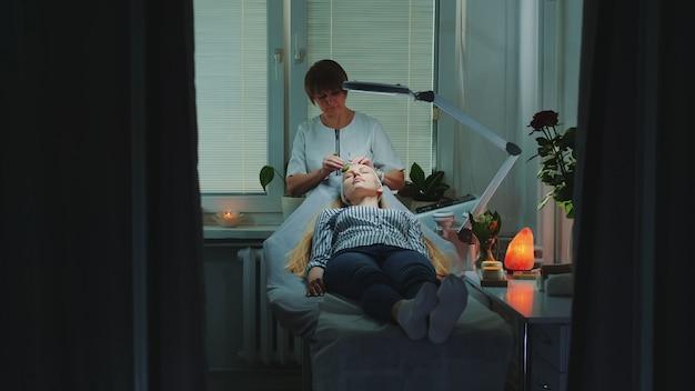 Esteticista fazendo massagem facial relaxante com rolo de jade no rosto de mulher em salão de beleza
