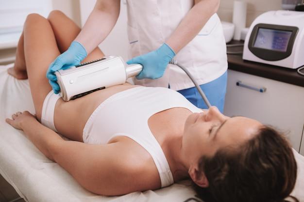 Esteticista fazendo procedimento de aperto de pele no estômago de uma cliente do sexo feminino