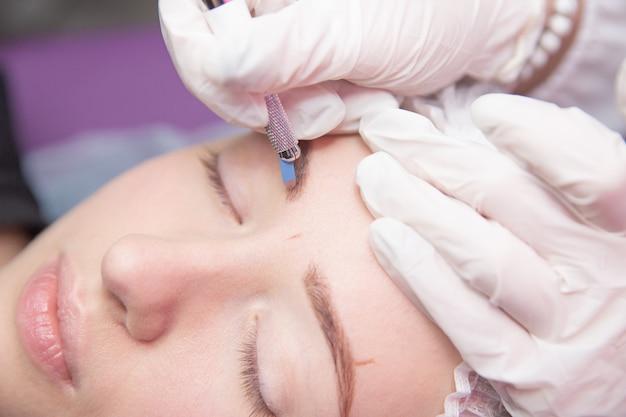 Esteticista fazendo tatuagem de sobrancelha para mulher