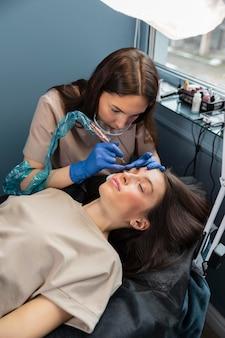 Esteticista fazendo um tratamento de sobrancelha para sua cliente