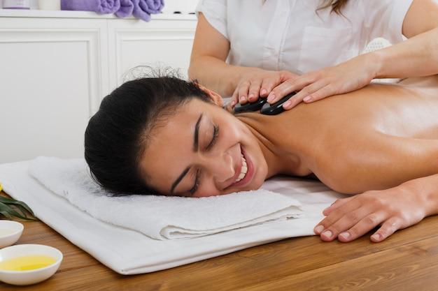 Esteticista fazer pedra massagem spa para mulher no centro de bem-estar