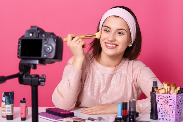 Esteticista feminina alegre usa pincel cosmético para aplicação de pó, registra o conteúdo viceo em seu blog, usa bandana