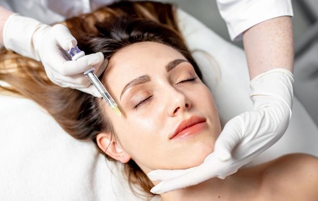 Esteticista feminina aplicando injeções nos lábios e no rosto de uma bela mulher em uma cunha cosmética