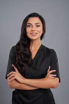Esteticista feminina atraente em uniforme preto em pé com os braços cruzados sobre um fundo cinza.