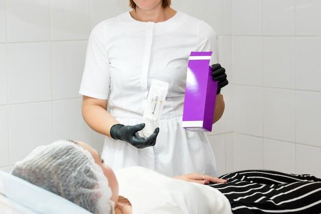 Esteticista feminina segurando o produto cosmético na clínica de beleza. sem rosto. médico, preparando o paciente para um procedimento cosmético.