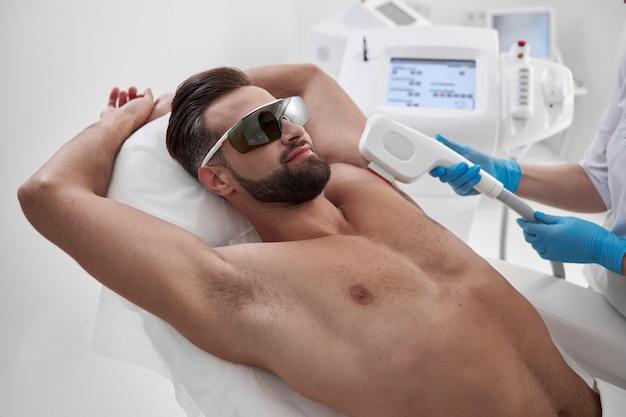 Esteticista habilidosa depila a axila de um cliente positivo, homem de meia-idade, com equipamentos modernos