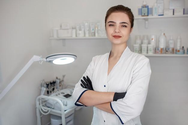 Esteticista jovem profissional ficar na sala de cosmetologia e pose. ela segura o hades cruzado. modelo parece confiante.