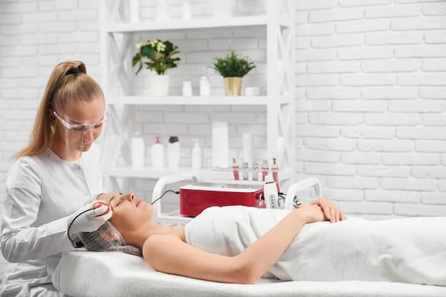 Esteticista limpando o rosto de uma jovem