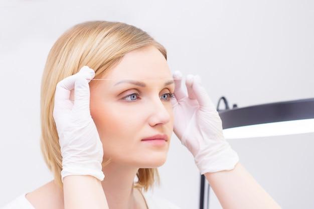 Esteticista marca as sobrancelhas com a ajuda da tatuagem de sobrancelha de fio