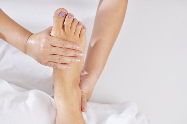 Esteticista massageando pés