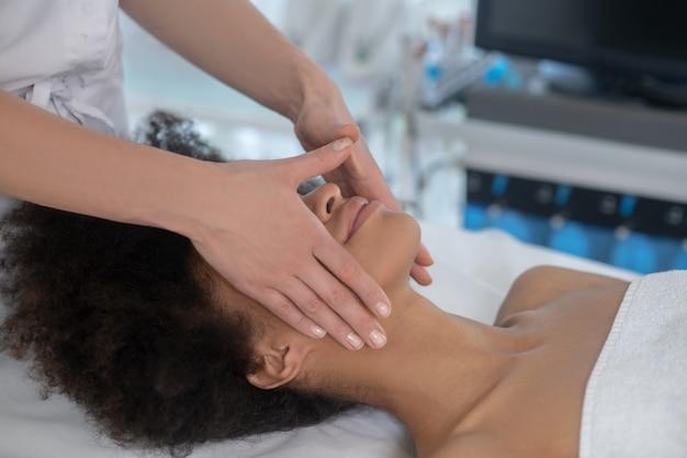 Esteticista, massagem. mulher jovem reclinada no sofá recebendo massagem facial no centro de cosmetologia e as mãos do médico
