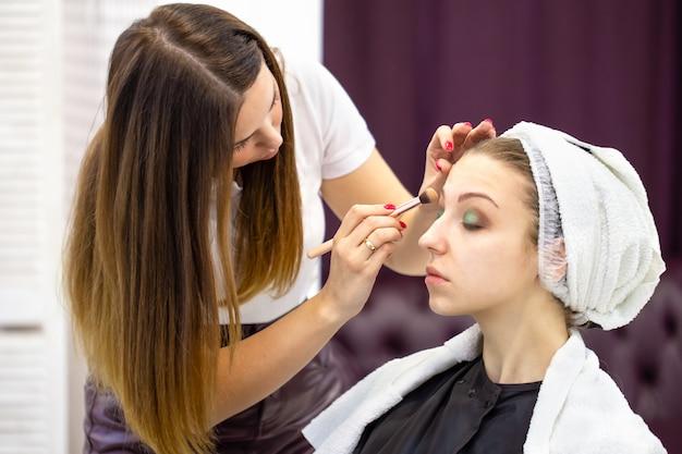 Esteticista pinta as pálpebras de uma linda jovem com uma escova cosmética