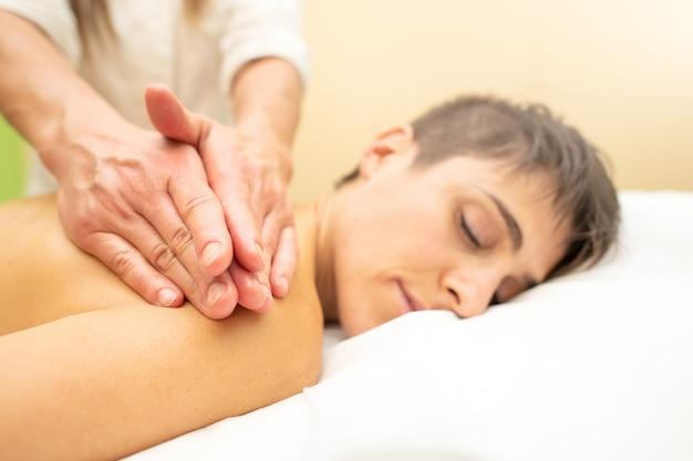 Esteticista pratica uma massagem estética relaxante atrás de uma jovem