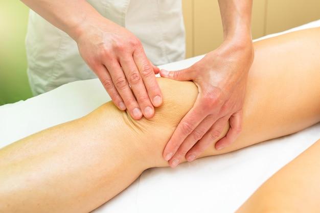 Esteticista pratica uma relaxante massagem no joelho