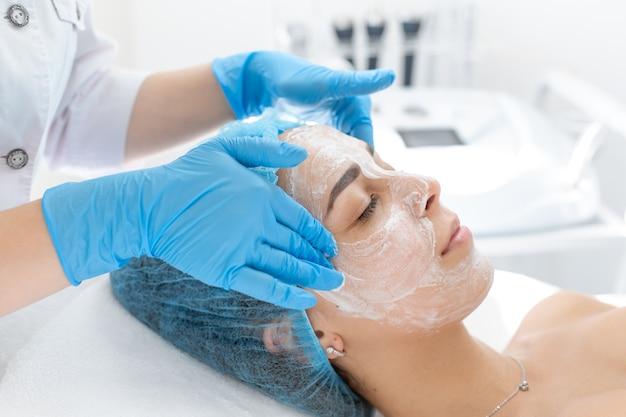 Esteticista profissional, mulher, aplica uma máscara no rosto de um paciente para cuidados com a pele